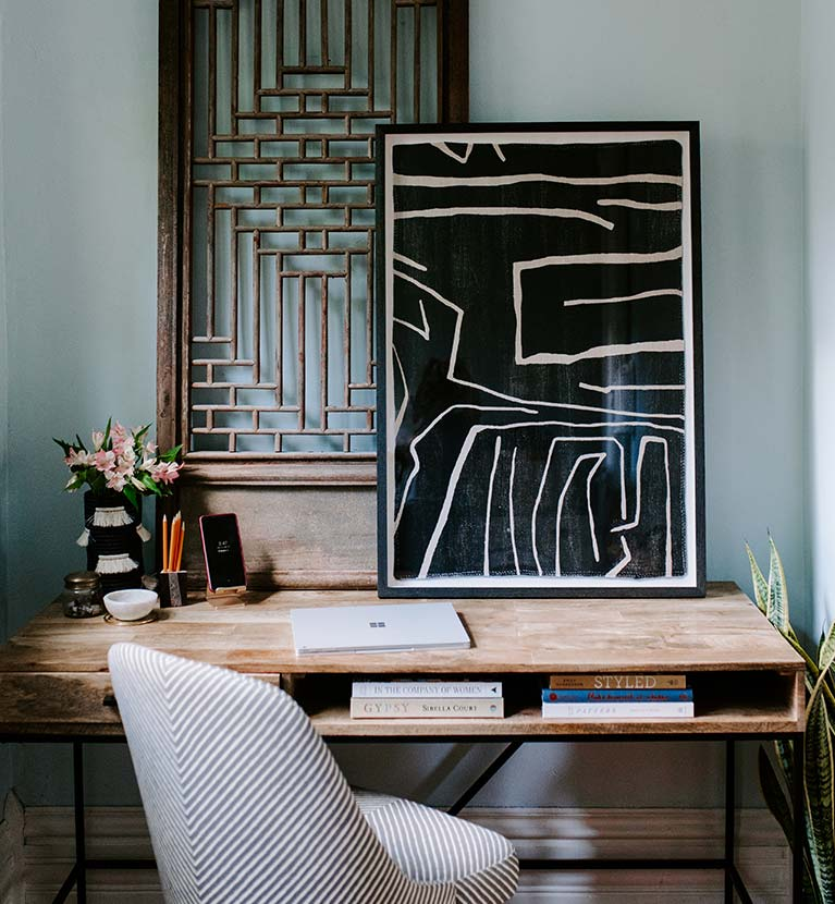 Beautiful wooden desk with books, art, flowers