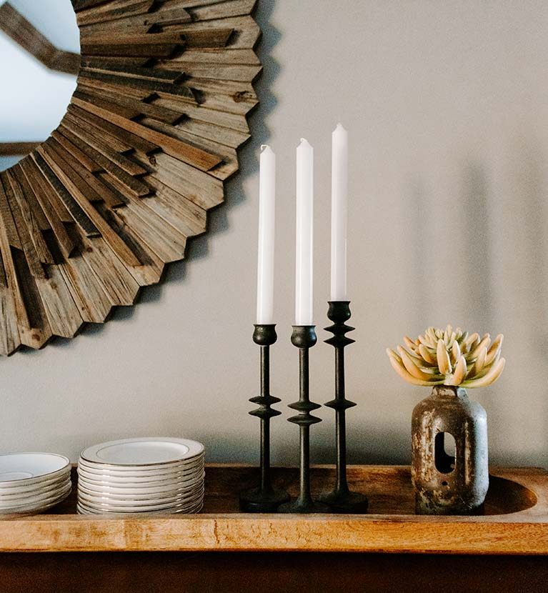 Wooden circular mirror frame behind three candlesticks and gold-rimmed china plates