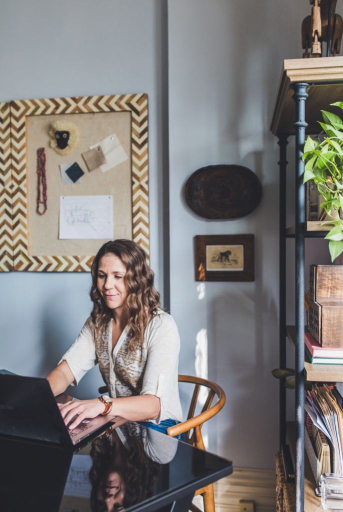 Founder Andrea Durcik works on a laptop in a room featuring sustainable design.