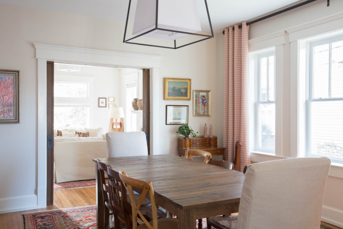 Dining room setting with a wooden table and a view into the living room.