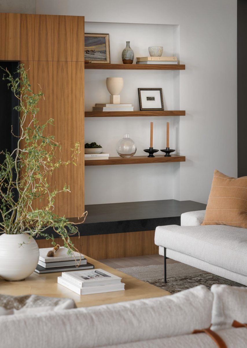 A Lisa Staton interior featuring a walnut finish shelf complimented by cream furniture and black marble surfaces.